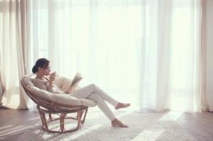 Frau in bequemem Sessel trinkt Tee liest