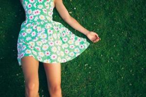 Junge Dame im Sommerkleid liegt in Wiese