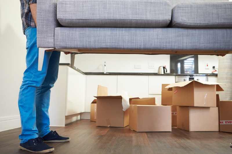 Student trägt Couch in neue Wohnung