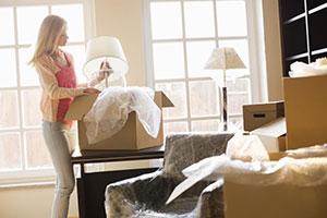Frau packt Lampe aus Umzugskarton aus