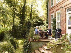 Mobiler Gas-Griller und Familie auf Terrasse