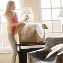 Frau packt nach Umzug Kartons aus