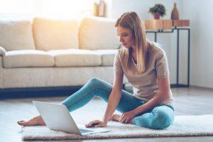 Frau meldet etwas in neuer Immobilie am Laptop an