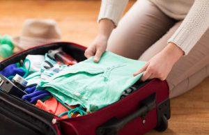 Frau packt Koffer für Wohnungstausch-Urlaub