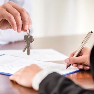 Mieter unterschreibt und erhält Immobilien-Schlüssel